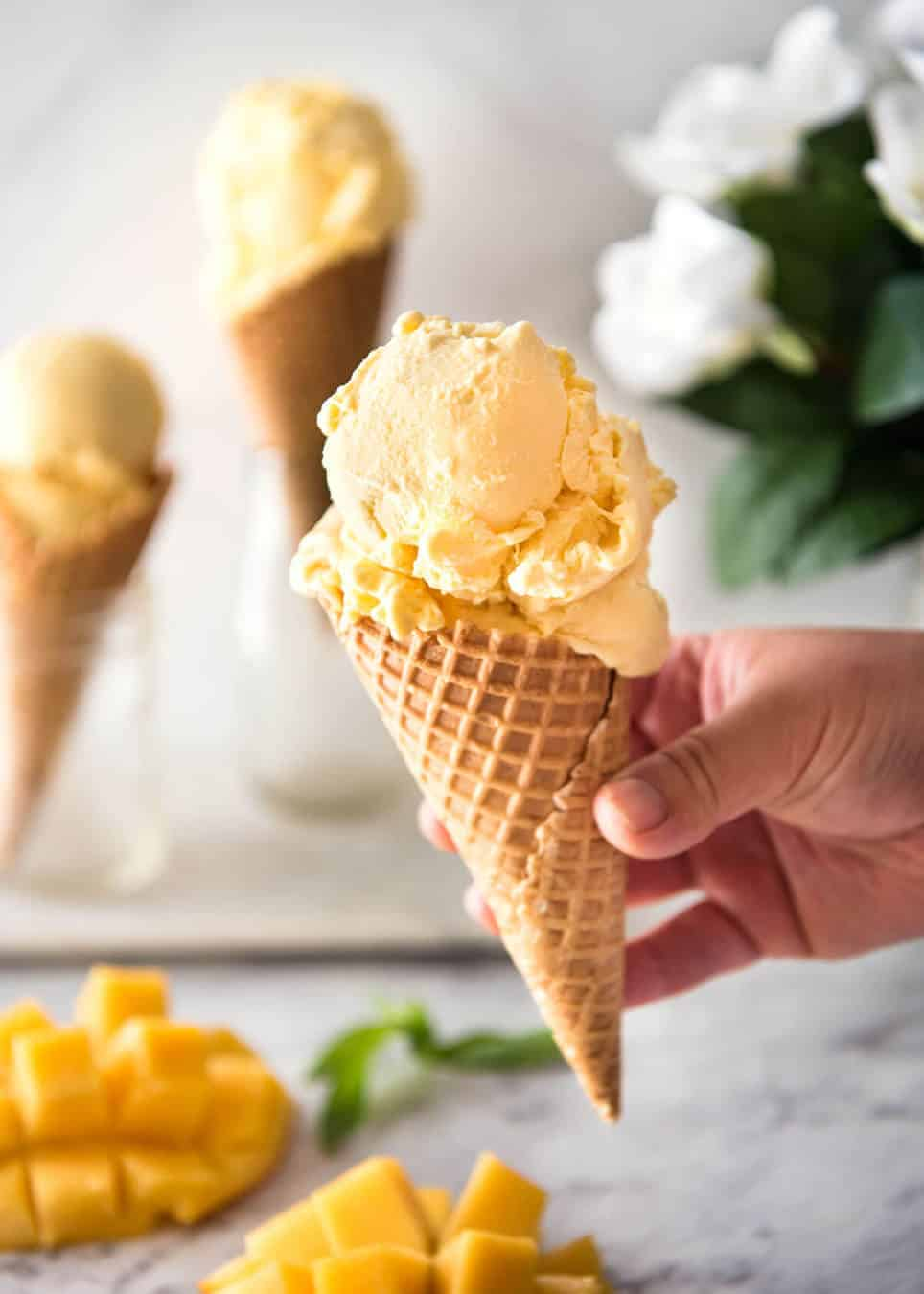 Ice cream cone with mango ice cream held in a hand.